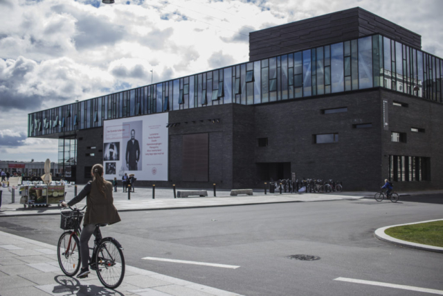 Národní divadlo získalo cenu za design a není divu. Kombinace černého kamene, kovu a skla působí minimalisticky a elegantně. Zajímavé je, že budova stojí napůl na souši a napůl nad vodou.
